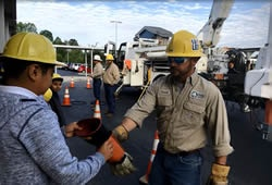 Linemen demonstrate safety gloves at local school.